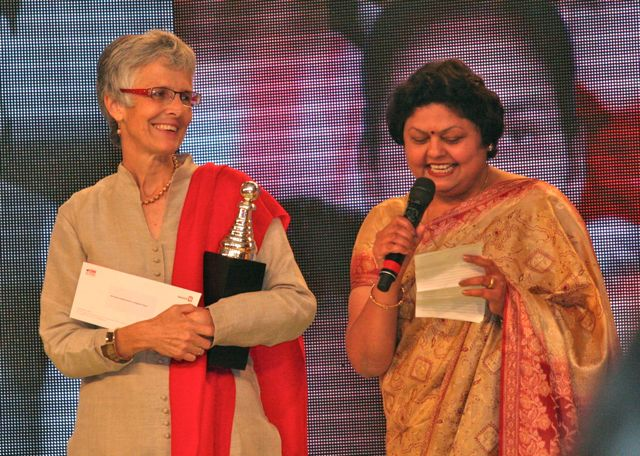 Jo and Manju, all dressed up, on stage. Manju with microphone; Jo with trophy and check
