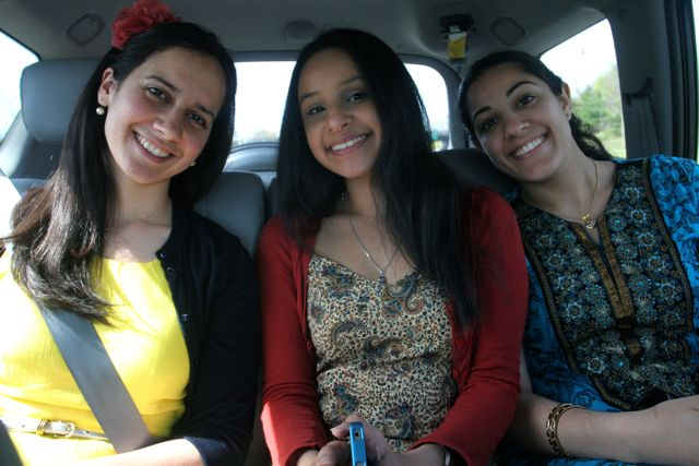 Three beautiful girls sitting in the backseat of a car