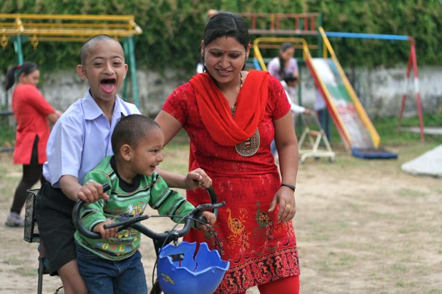 Small boy and older boy with Down Syndrom on adapted bicycle while teacher helps from the side