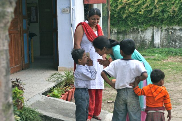 Small boy does Namaste to his teacher; two children and a teacher look on from the side