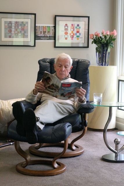 Elderly man in black leather chair, reading a magazine. Flowers behind him.