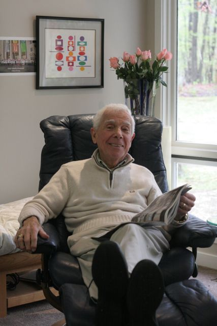 Elderly man in leather chair, holding a magazine, smiling.