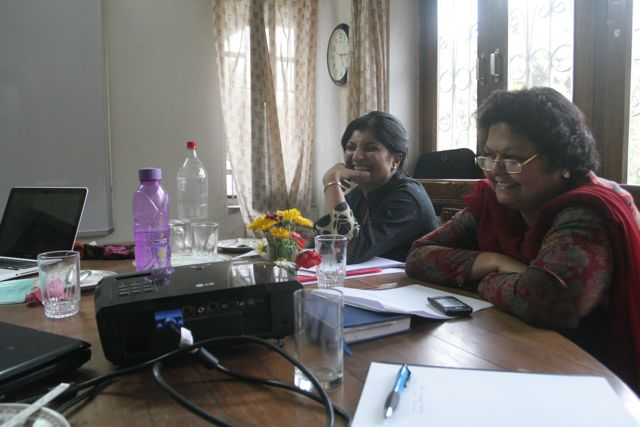 Two women at a meeting table, laptops open, water bottles and flowers on table