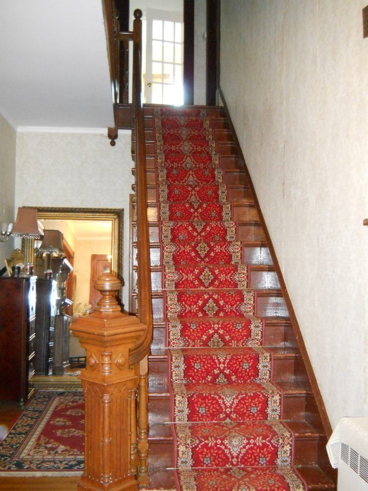 Old fashioned hallway, sweeping staircase with beautiful red carpeting