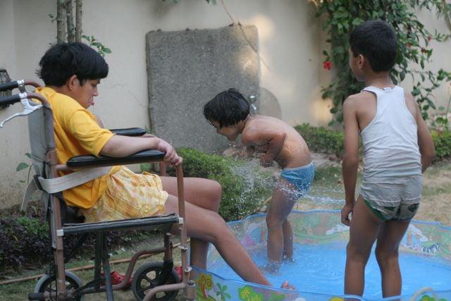 Three children, one in a wheelchair - enjoying a wading pool