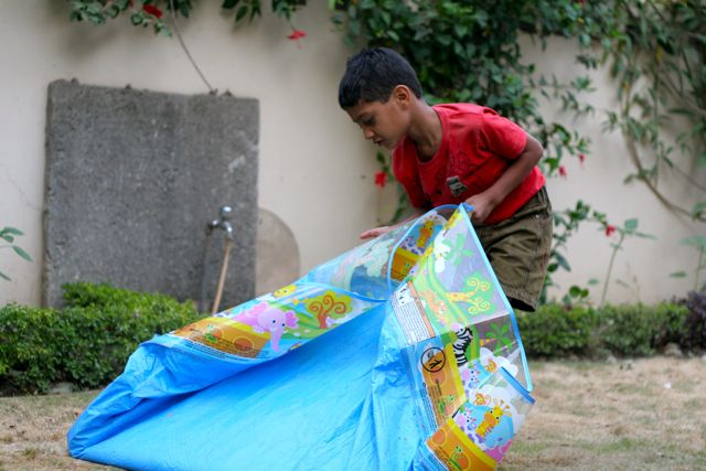 Boy in red shirt emptying a wading pool