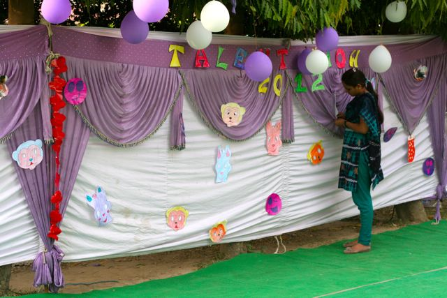 Stage backdrop for talent show - white hangings, purple drapes