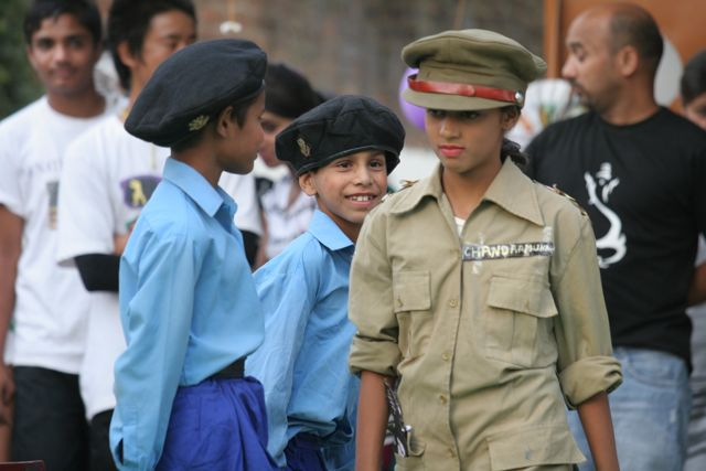 Girl dressed as policewoman passes two junior policemen