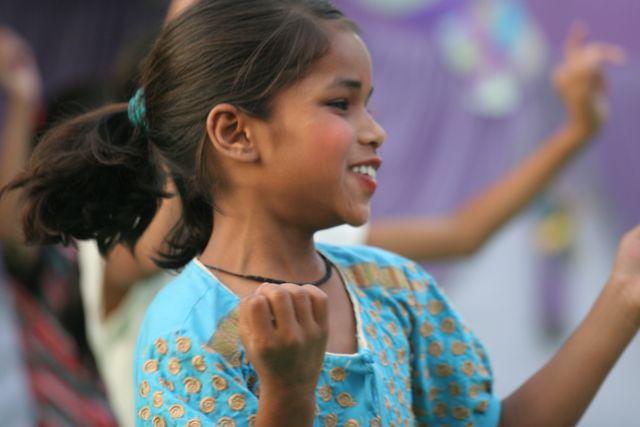 Girl in blue, smiling, dancing