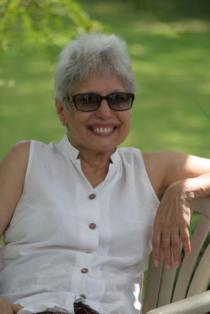 Anu Aga, white hair,  smiling, green grass in background,