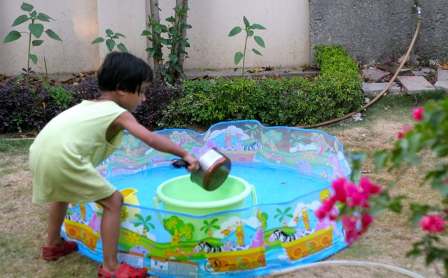 Little girl playing beside a wading pool