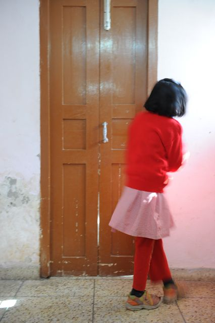 Girl in red sweater, back to the camera,  just off target for the door she is seeking