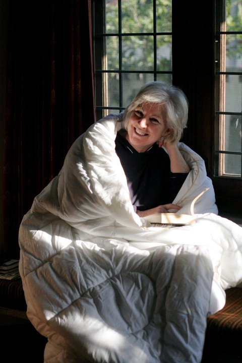 Woman with white hair, wrapped in a white quilt, sitting in a window seat, sun streaming in