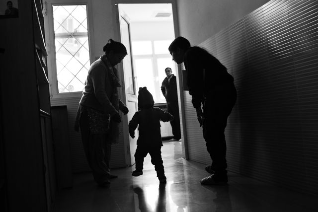Child walking ahead of two adults, unsteady on his feet, into an open doorway