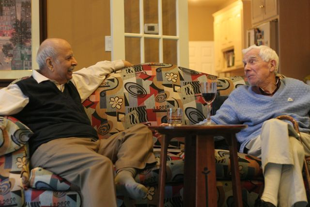 Two elderly men on a couch, smiling across at each other