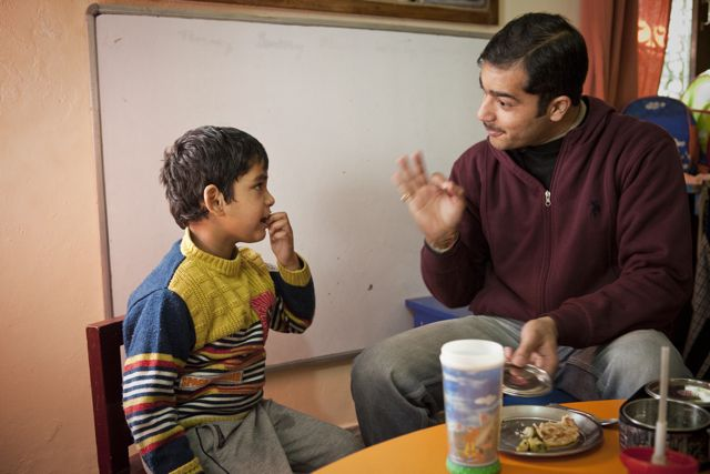Teacher with child at the lunch table. Child is feeding himself; teacher signing approval.