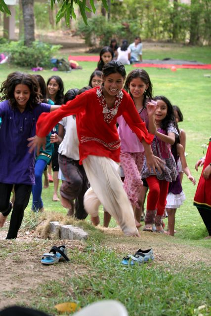 Children running gleefully up a green hill