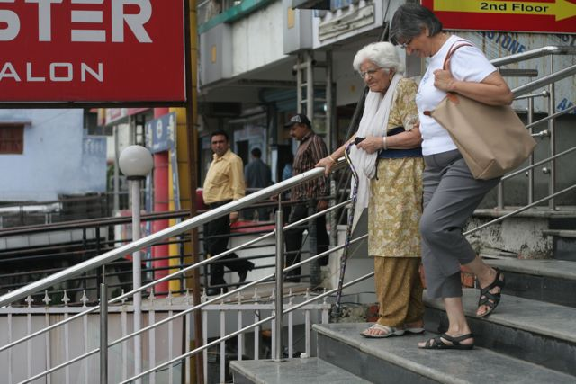 Middle-aged woman assists elderly woman with a cane down the stairs