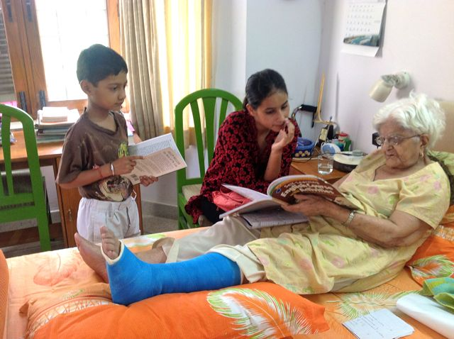 Elderly woman, leg in a cast, teaches children from her bed