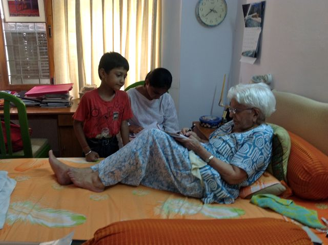 Elderly Indian woman on a bed, teaching two children