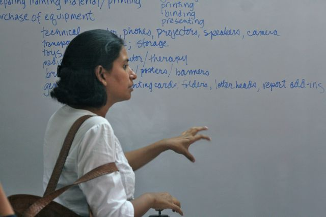 Woman standing in front of a white board covered with notes about a proposal