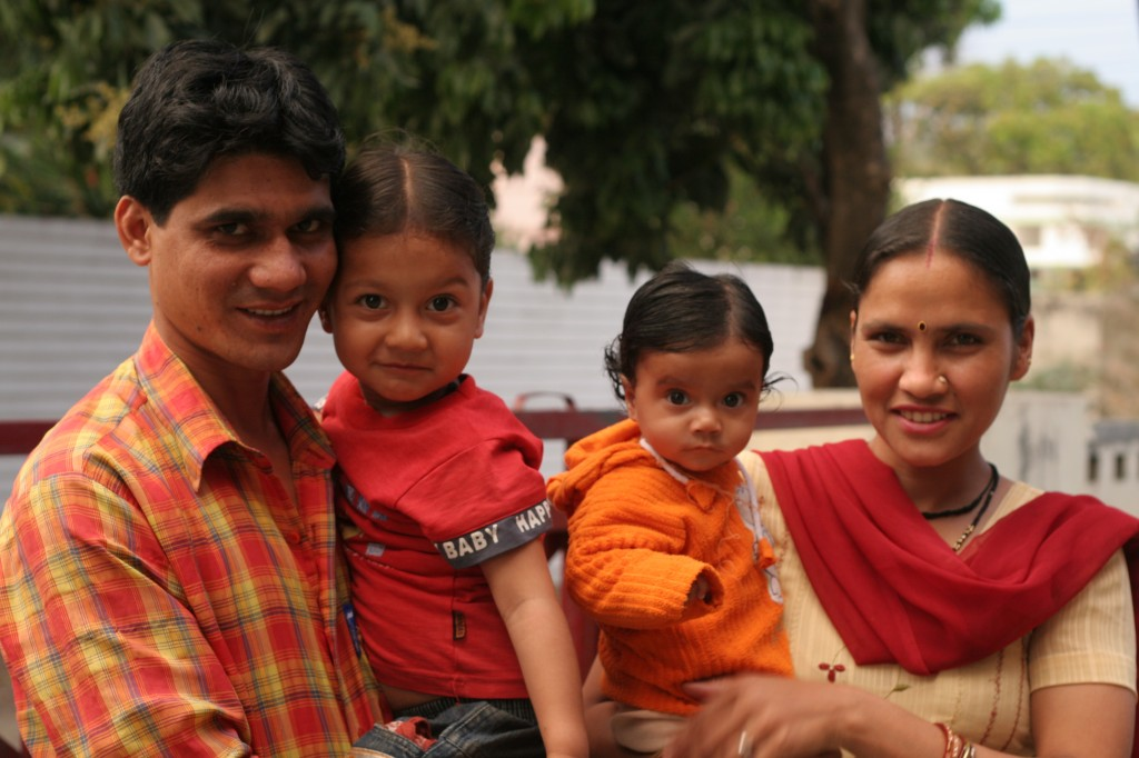 Indian family portrait: father holding little boy, mother holding infant girl