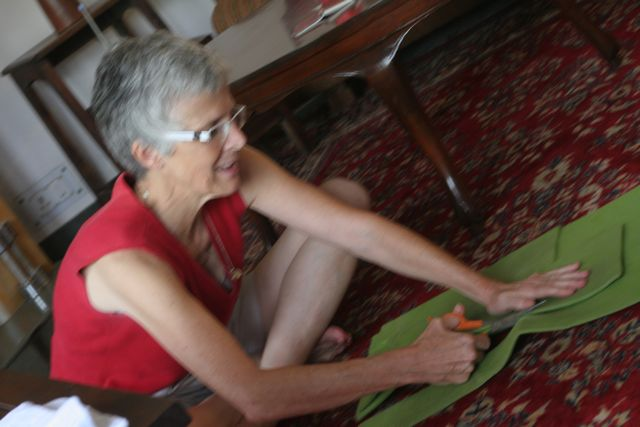 Woman cutting green foam yoga mat