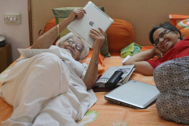 elderly woman with her daughter on a bed, learning how to use an I-pad