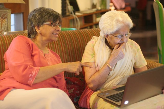 Woman teaching her elderly mother how to use a laptop