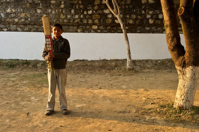 Boy stands proudly with cricket bat in empty playing field