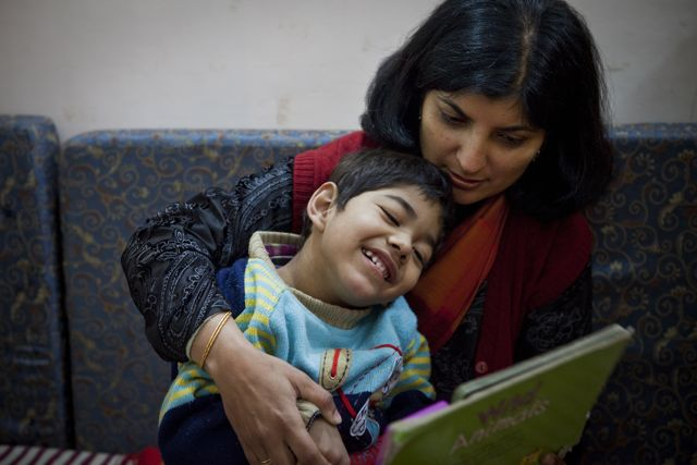 Teacher holds child in her arms while reading a storybook to him