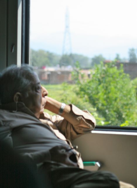 Elderly man sitting gazing out a train window; green fields, mountains in distance