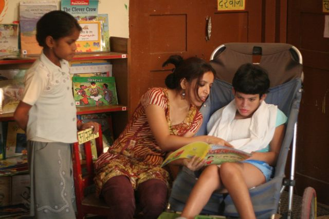 Teacher reads t  child in wheelchair while a second child watches from the side