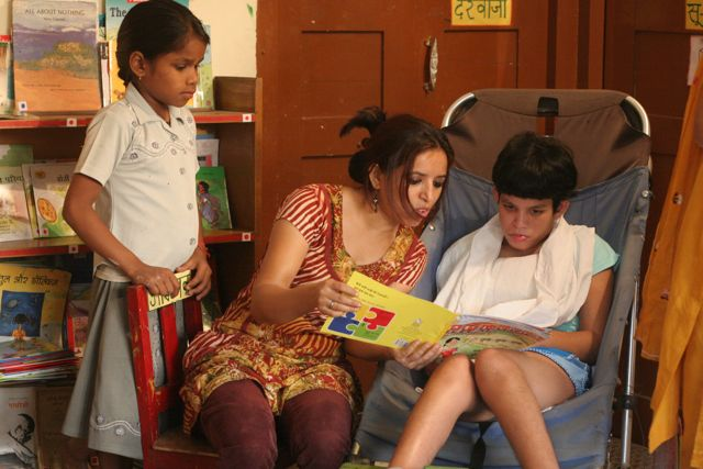 Teacher continues to read, child on sidelines moves in closer