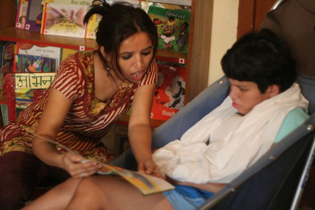 Teacher reads a story to a child in a wheelchair