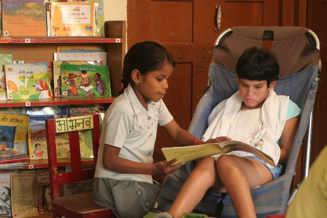 Child sits with girl in wheelchair and they read a story together