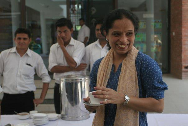 Attractive woman, holding a tea cup, smiling. Waiters at a buffet behind her.
