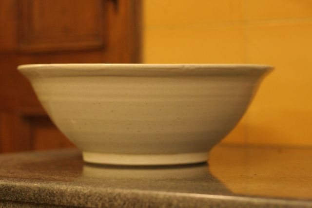 a large white mixing bowl on a grey counter, with a yellow tiled backgrown