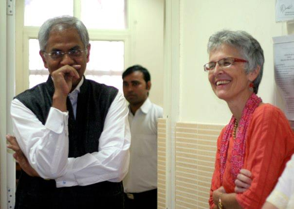 Handsome Indian man in white shirt and black vest smiling; American woman in red listening beside him (also smiling)