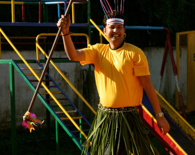 Tall Indian man in yellow t-shirt and a grass skirt, brandishing a pretend tribal spear