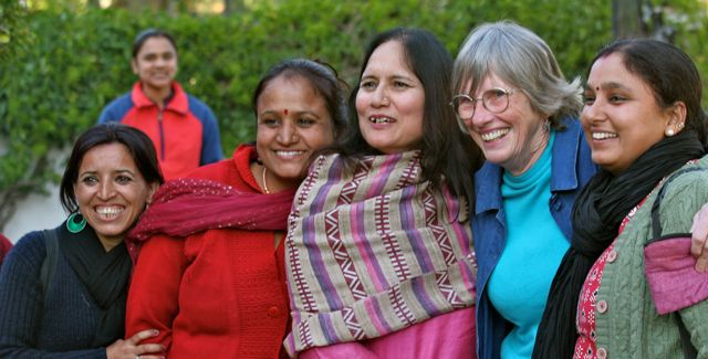 Row of Indian women (with one Brit in the centre) standing together, smiling