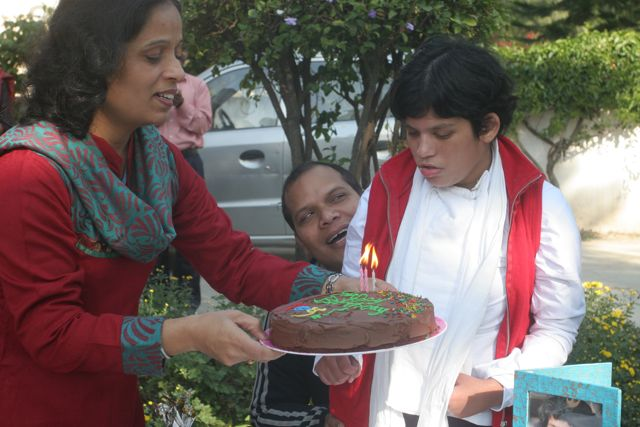 Attractive woman, holding a birthday cake in front of a pretty girl