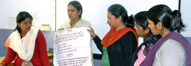 Five ASHA workers making a presentation - two are holding a poster with Hindi script about child development