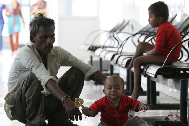 Father and two children in an Indian hospital corridor