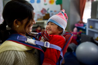 Baby with a disability beams at his mother while sitting in his baby-sling