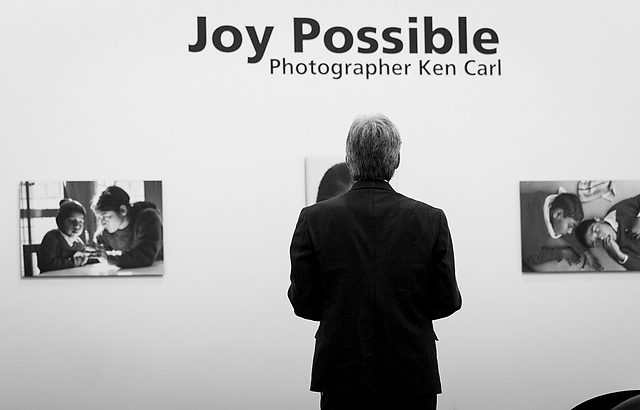 Black and white photo of a man looking at pictures in a gallery - title reads: Joy Possible.