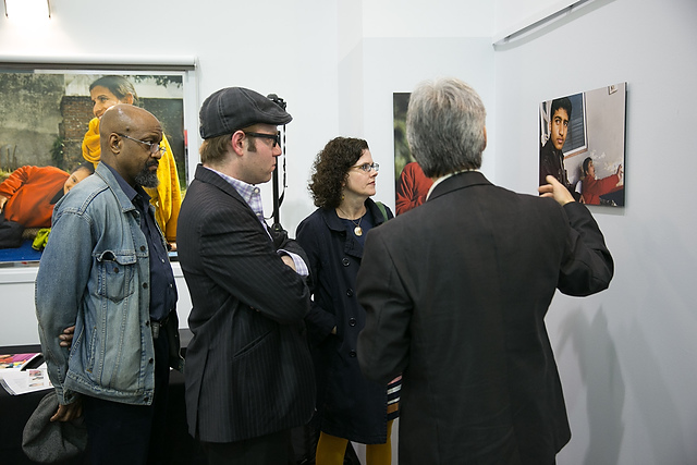 Photographer explaining his work  to visitors to the exhibition