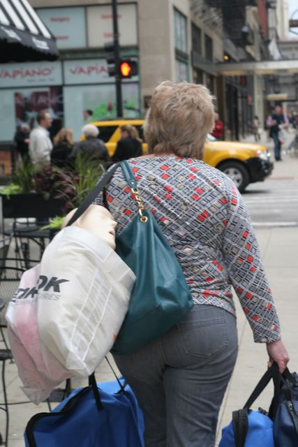 Woman photographed from behind, carrying many shopping bags, one of which has a mannequin's head poking out