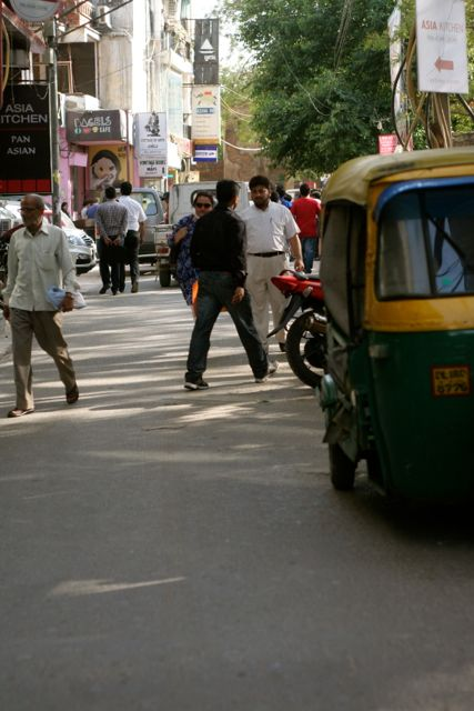 Street scene in India - rickshaw in foreground; people crossing the street