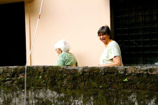 Elderly woman walking down an alley; younger woman looking triumphant!